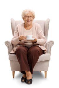 een lachende oude vrouw, zittend in een stoel met een kopje koffie
